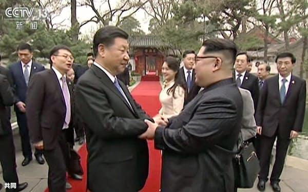 中国中央テレビが28日放映した、北京の釣魚台迎賓館で握手する中国の習近平国家主席(左)と北朝鮮の金正恩朝鮮労働党委員長の映像=共同