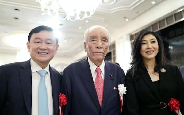 石井一元自治相(中)と記念写真を撮るタイのインラック前首相(右)と兄のタクシン元首相(29日、都内)
