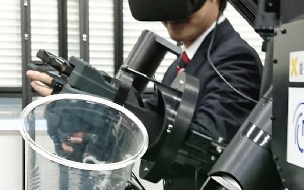触覚のあるロボットを操作し、コップを右手から左手に持ち替える(横浜市の慶応大)