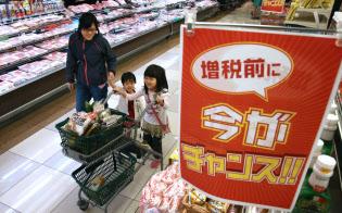 14年の消費増税前日に買い物をする家族連れ。今回の骨太方針原案では19年度と20年度の当初予算で景気対策を組む方針