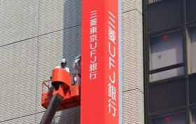 「三菱UFJ銀行」に名称を変更して看板の掛け替えをする作業員(1日午前、東京都千代田区)