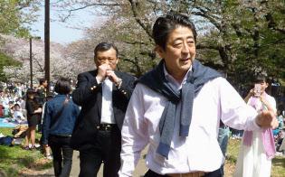 セーターを肩に掛けて散歩する安倍首相(1日午後、東京都渋谷区の代々木公園)=共同