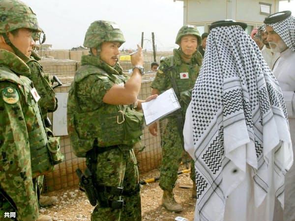 2006年5月、イラク南部サマワの陸上自衛隊宿営地で、地元住民と話す隊員ら(共同)