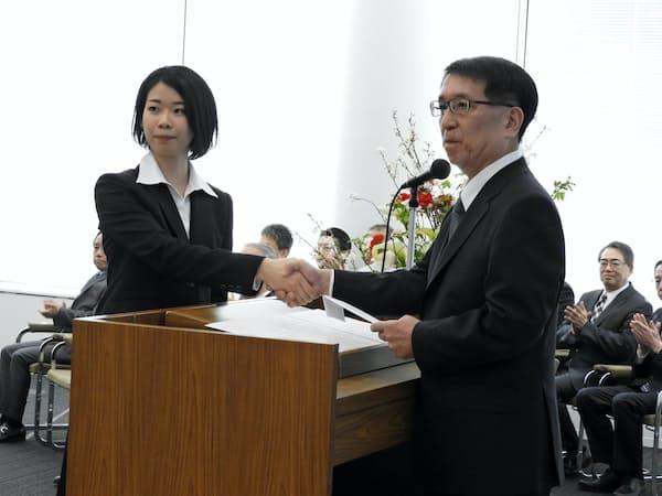 入行式で新入行員と握手する北洋銀の安田頭取(2日、札幌市)