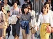 気温が上がり、上着を脱いで歩く人たち(4日午後、名古屋市中村区)