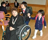終業式で宮城まり子さんの車いすを押す「ねむの木学園」の子供たち(静岡県掛川市)=共同