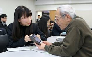 災害時のスマホ活用法を高齢者に教える学生(1月、熊本市中央区の熊本学園大)