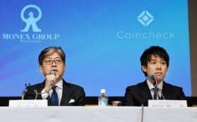 記者会見するマネックスグループの松本大社長(左)とコインチェックの和田晃一良社長(6日午後、東京都港区)