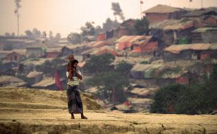 日没後、高台に立つ親子。現在、この最大規模のキャンプだけで62万人が暮らす。乾いた風に吹き上げられた砂が屋根に降り積もり、茶色にくすんだテントの群れがはるか遠くまで続いていた(3月29日、バングラデシュ・コックスバザールのクトゥパロン・バルカリ難民キャンプ)