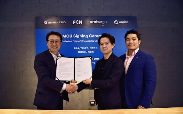 新韓カードのキム・ジョンスデジタルビジネス部門長(左)と握手するオミセHDの長谷川潤社長(中央)=オミセHD提供