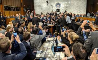 Tシャツではなくスーツを着たザッカーバーグ氏を、多数の報道陣が取り囲んだ(ワシントン、10日)