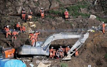山が崩落し民家が埋もれた現場で続けられる捜索活動(11日夜、大分県中津市)=塩山賢撮影