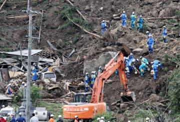 山崩れで民家が巻き込まれた現場で捜索活動をする大分県警の警察官ら(11日、大分県中津市)