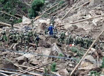 山崩れで民家が巻き込まれた現場で捜索活動をする自衛隊員ら(11日、大分県中津市)