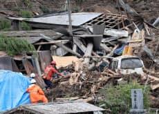 山崩れで民家が巻き込まれた現場で行われる救助活動(11日、大分県中津市)