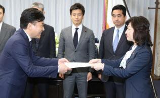 野田総務相(右)から「4G」電波の割り当て認定書を受け取る楽天の三木谷社長(9日午後、総務省)