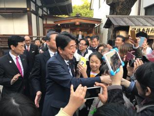 大阪天満宮で参拝客らと握手する安倍首相(13日、大阪市)