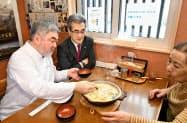 「大雪山大学」のラーメンの試食会に参加したフランス料理のシェフ、三国清三さん(左)(3月、北海道上川町)=共同