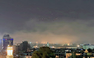 米英仏軍によるシリアへの軍事攻撃が始まり、対空砲火と煙があがるダマスカス上空(14日)=AP
