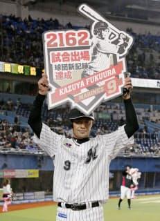 福浦は球団の最多出場記録を更新し、記念のボードを掲げた=共同