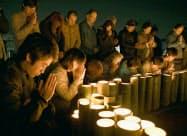 熊本地震の「本震」から2年を迎えた熊本県益城町の木山仮設団地で、地震の発生時刻に手を合わせ黙とうする被災者ら(16日未明)=共同