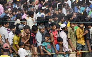 雨期を前に住居用の資材を求めて行列をつくるロヒンギャ難民(3月31日、バングラデシュのコックスバザール)=柏原敬樹撮影