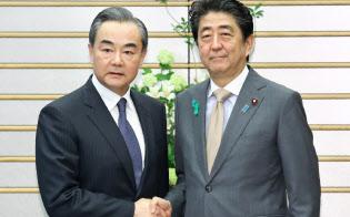 会談を前に中国の王毅外相(左)と握手する安倍首相(16日午後、首相官邸)
