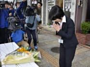 献花台に花をささげ、手を合わせる長崎市職員(17日午前、長崎市)=共同