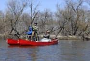 北海道・釧路湿原を流れる釧路川で、カヌーに乗って釣りを楽しむ人たち(17日、共同)