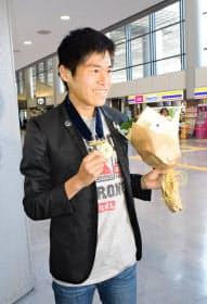 ボストンマラソン優勝のメダルを手に笑顔の川内(19日、成田空港)