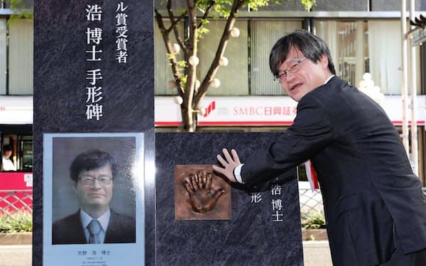 自身の手形のモニュメントに手を合わせるノーベル賞受賞者の天野浩さん(19日午後、名古屋市中区)