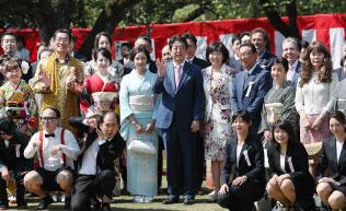 「桜を見る会」で参加者と記念写真に納まる安倍首相(21日午前、東京・新宿御苑)