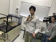 精密切断機の使い方を説明する県産業技術研究所の職員(25日、松山市)
