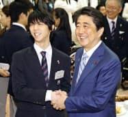 首相官邸で安倍首相(右)と握手するフィギュアスケートの羽生結弦選手(26日午後)=共同