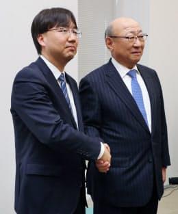 任天堂の次期社長に決まり握手する古川俊太郎取締役(左)と君島達己社長(26日、大阪取引所)