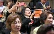 南北両首脳が映るテレビ中継をスマートフォンで撮影する人たち(27日午前、大阪市北区の大阪韓国文化院)