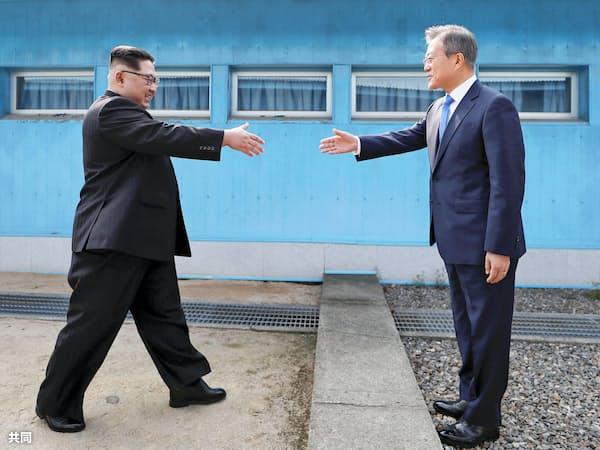 9時29分ごろ 軍事境界線を挟み握手する金委員長(左)と文大統領=韓国共同写真記者団・共同