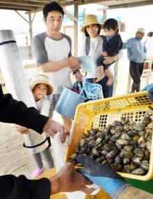 潮干狩りで採った貝と交換される無害な貝(22日、大阪府貝塚市)