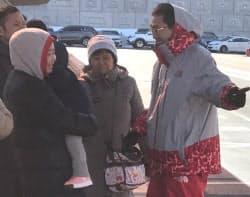 厳しい冷え込みの中、バス停で案内役を務める平昌冬季五輪のボランティア(2月、平昌)