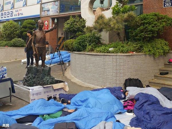 韓国・釜山の日本総領事館付近まで運ばれた徴用工像。下は寝袋に入り一夜を明かした人たち(1日)=共同