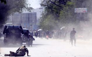カブールでのテロで2度目の爆発が起き、地面に伏せる治安部隊兵士ら(4月30日)=AP