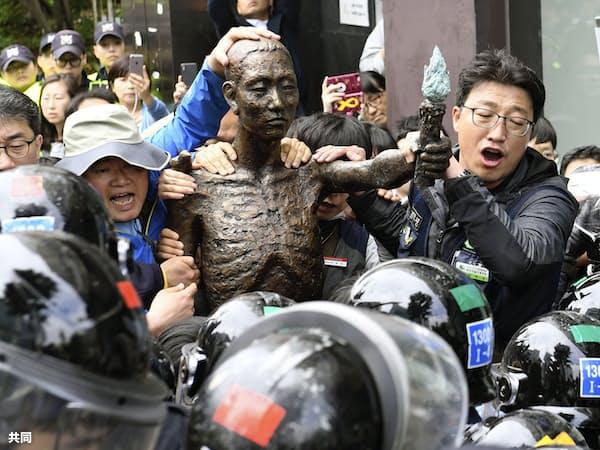 韓国・釜山の日本総領事館付近で、徴用工像を巡り警官隊ともみ合う労働団体メンバーら(1日)=共同