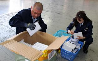 空路で輸入された貨物を検査する税関職員(東京都江東区)