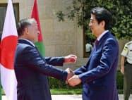 ヨルダンのアブドラ国王(左)と握手する安倍首相(1日、アンマンの王宮府)=共同