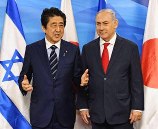 2日、エルサレムの首相府でイスラエルのネタニヤフ首相に出迎えられ、あいさつする安倍首相=共同