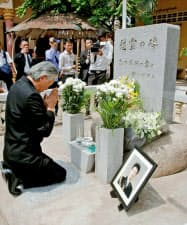 高田晴行警視の慰霊碑の前で手を合わせる堀之内秀久駐カンボジア大使(4日)=共同