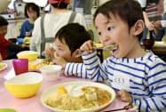 食物アレルギー対応の料理を頬張る子どもたち(4月28日、滋賀県守山市の福祉保健センター)=共同