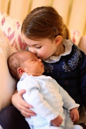 英ロンドンのケンジントン宮殿でルイ王子のおでこにキスするシャーロット王女(2日)=キャサリン妃撮影・AP