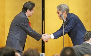 石原派のパーティーで握手する自民党の石原伸晃氏(右)と安倍首相(7日午後、東京都港区)