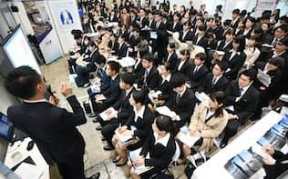 合同企業説明会で企業の担当者の話を聞く就活生(3月、千葉市美浜区の幕張メッセ)